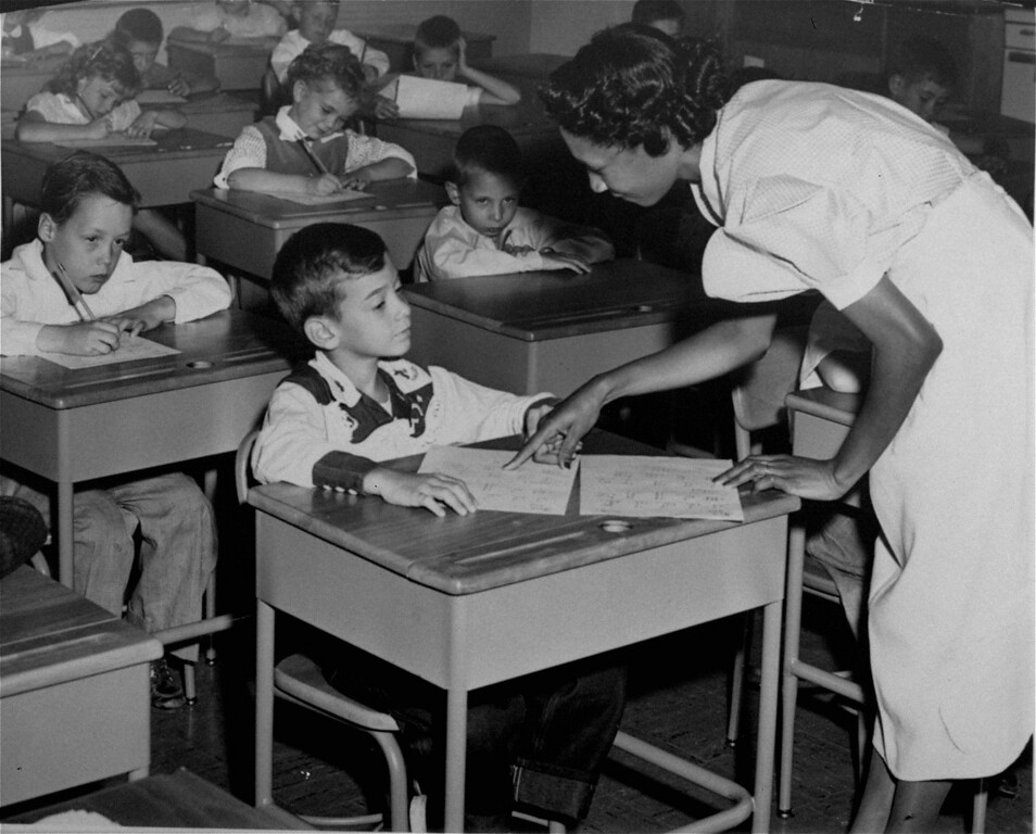 . Mrs. Ella J. Rice, talks to one of her pupils, all of whom are white, in a third grade classroom of the Draper Elementary School in southeast Washington, D.C., September 13, 1954.  This is the first day of non-segregated schools both as to teacher and pupils, in the District of Columbia public school system.  Mrs. Rice is the only black teacher in the school. (AP Photo)
