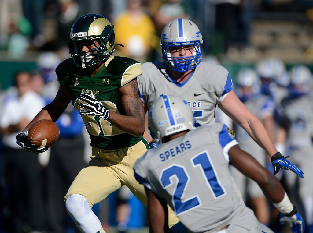 . Colorado State WR, Rashard Higgins, left, looks for extra room on a long completion play against Air Force DL, Riley Cannon, center, and Air Force DB, Christian Spears, bottom right, in the first quarter at Hughes Stadium  Saturday afternoon, November 30, 2013. (Photo By Andy Cross/The Denver Post)