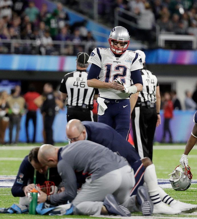 . New England Patriots quarterback Tom Brady (12) looks as Brandin Cooks, bottom, is tended to after being hit during the first half of the NFL Super Bowl 52 football game against the Philadelphia Eagles Sunday, Feb. 4, 2018, in Minneapolis. (AP Photo/Mark Humphrey)