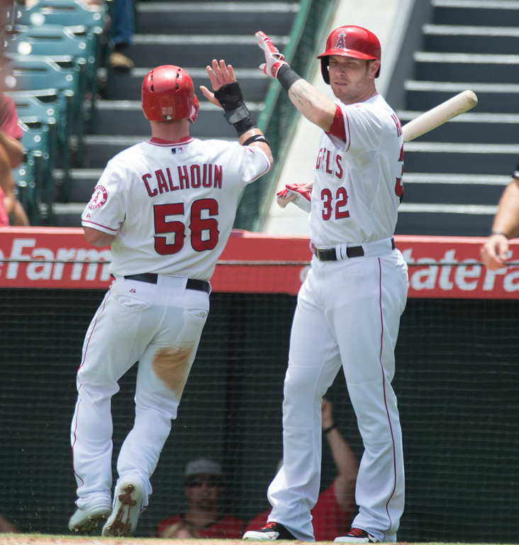. Angels\' Kole Calhoun (#56) is congratulated by Josh Hamilton after scoring against the Minnesota Twins at Angel Stadium in Anaheim on Thursday June 26, 2014. (Photo by Keith Durflinger/Whittier Daily News)