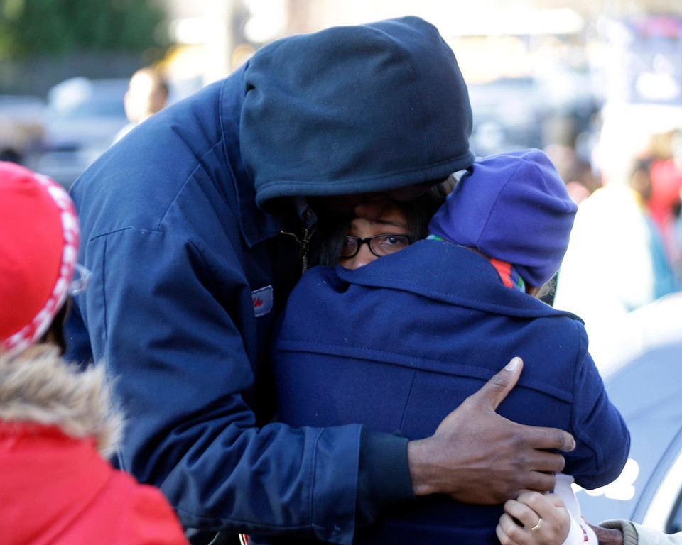 . A man and a woman are reunited with a child a child after after a shooting at an Price Middle school in Atlanta Thursday, Jan. 31, 2013. A 14-year-old boy was wounded outside the school Thursday afternoon and a fellow student was in custody as a suspect, authorities said. No other students were hurt. (AP Photo/John Bazemore)