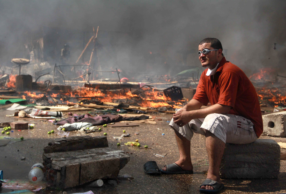 . A supporter of the Muslim Brotherhood and Egypt\'s ousted president Mohamed Morsi looks on during clashes with security forces in Cairo on August 14, 2013, as security forces backed by bulldozers moved in on two huge pro-Morsi protest camps, launching a long-threatened crackdown that left dozens dead. The clearance operation began shortly after dawn when security forces surrounded the sprawling Rabaa al-Adawiya camp in east Cairo and a similar one at Al-Nahda square, in the centre of the capital.  MOSAAB EL-SHAMY/AFP/Getty Images