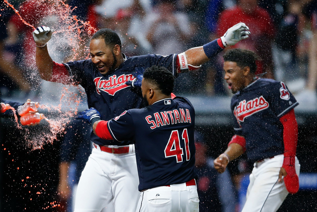 . Cleveland Indians\' Edwin Encarnacion, left, celebrates with Carlos Santana (41) and Francisco Lindor after hitting a game-winning grand slam off Los Angeles Angels\' Bud Norris during the 11th inning of a baseball game, Tuesday, July 25, 2017, in Cleveland. The Indians won 11-7. (AP Photo/Ron Schwane)