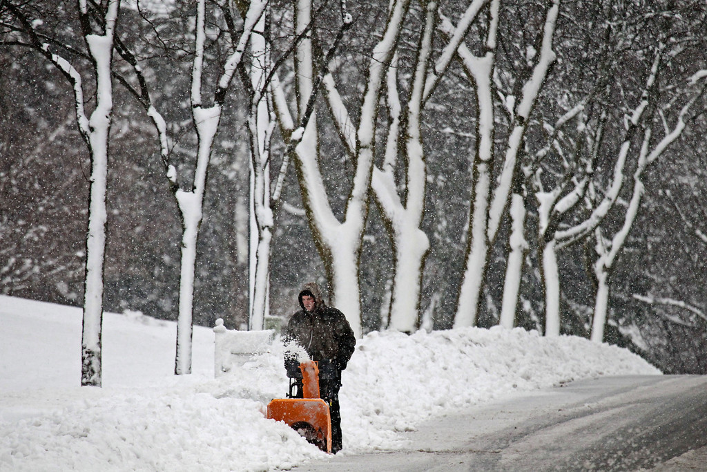 . A man uses a snowblower to clear away a walkway on the 1400 block of Chestnut Street in West Bend, Wis, Thursday, Dec. 20, 2012. (AP Photo/Milwaukee Journal-Sentinel, Michael Sears)