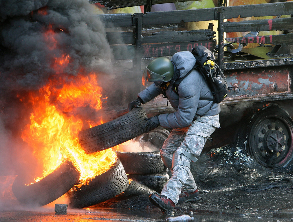 . An protester throws tires on a barricade during the continuing protest in downtown Kiev, Ukraine, 18 February 2014.   EPA/IGOR KOVALENKO