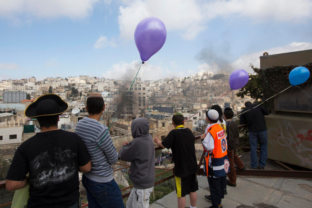 Description of . Young Jewish settlers, some dressed in costume to celebrate the holiday of Purim, watch as smoke rises from clashes between Israeli soldiers and Palestinians during a protest in the West Bank city of Hebron February 24, 2013. Purim is a celebration of the Jews\' salvation from genocide in ancient Persia, as recounted in the Book of Esther. REUTERS/Ronen Zvulun
