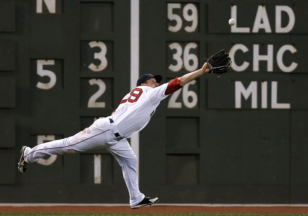 . Boston Red Sox left fielder Daniel Nava can\'t make a running catch on a long single by Colorado Rockies\' Carlos Gonzalez during the seventh inning of a baseball game at Fenway Park in Boston Tuesday, June 25, 2013. (AP Photo/Winslow Townson)