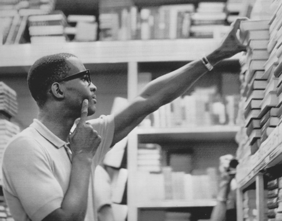 . James Hood reaches for a book on a shelf of the university bookstore on the campus of the University of Alabama in Tuscaloosa on June12, 2013. Hood, and another black student, Vivian Malone, were admitted yesterday. (The Denver Post Archive)