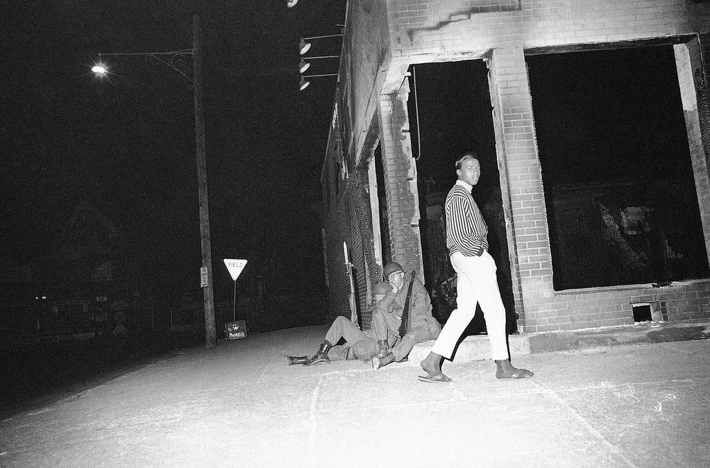 . Two National Guardsmen appear to be in relaxed boredom in Cleveland, Ohio, July 23, 1966 as violence and vandalism in the riot area apparently tapered off last night in the aftermath of rioting the last three nights. (AP Photo)