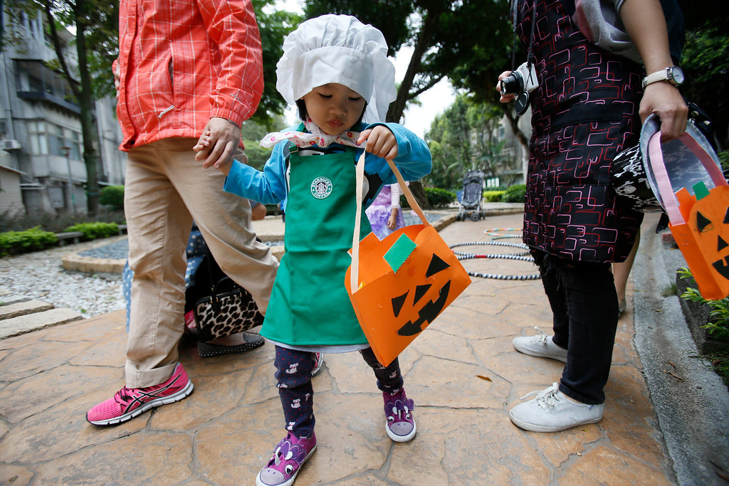 . A young girl in costume celebrating Halloween checks her collection of candies from local shops in Taipei, Taiwan, Thursday, Oct. 31, 2013.  (AP Photo/Wally Santana)