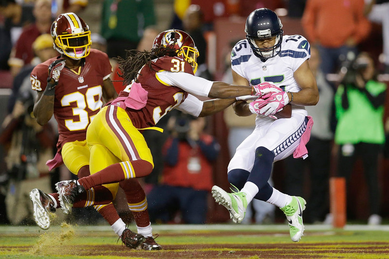 . Seattle Seahawks wide receiver Jermaine Kearse (15) pulls in a touchdown pass as Washington Redskins strong safety Brandon Meriweather (31) reaches to grab the ball during the first half of an NFL football game in Landover, Md., Monday, Oct. 6, 2014. (AP Photo/Patrick Semansky)