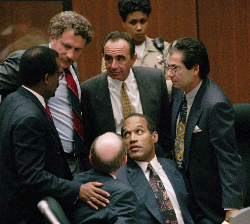 . Double-murder defendant O.J. Simpson is surrounded by his Dream Team defense attorneys from left, Johnnie L. Cochran Jr., Peter Neufeld, Robert Shapiro, Robert Kardashian, and Robert Blasier, seated at left, at the close of defense arguments Thursday, Sept. 28, 1995, in Los Angeles. (AP Photo/Sam Mircovich, pool)