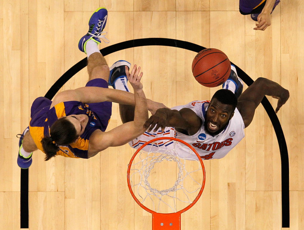 . ORLANDO, FL - MARCH 20:  Patric Young #4 of the Florida Gators and John Puk #44 of the Albany Great Danes battle for a rebound during the second round of the 2014 NCAA Men\'s Basketball Tournament at Amway Center on March 20, 2014 in Orlando, Florida.  (Photo by Mike Ehrmann/Getty Images)