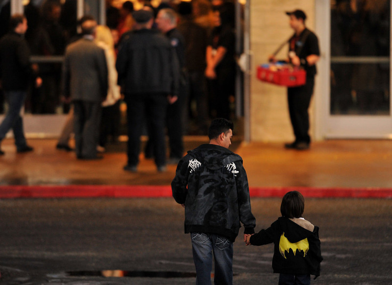 . AURORA, CO - JANUARY 17: A youth wearing Batman logo shirts is escorted to the Century Aurora. The movie theater where a gunman killed 12 people and wounded dozens of others reopened with a private ceremony for victims, first responders and officials. (Photo By Hyoung Chang / The Denver Post)