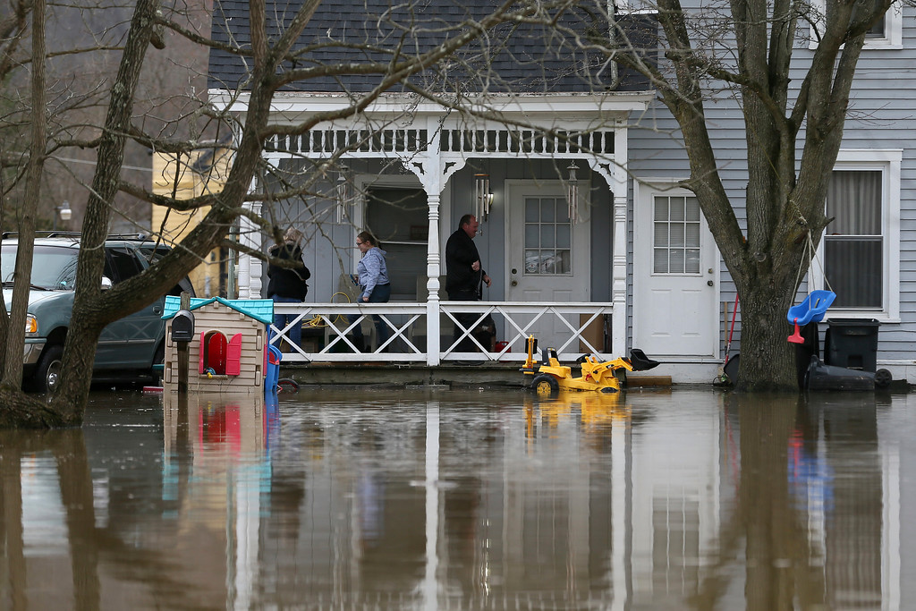 . A family walks on their front porch as flood waters surround their home Sunday, Feb. 25, 2018, in Cincinnati. Heavy rains overnight have sent the swollen Ohio River at Cincinnati to its highest point in 20 years with the river expected to remain above flood stage through the end of the week, a National Weather Service meteorologist said Sunday. (Kareem Elgazzar/The Cincinnati Enquirer via AP)