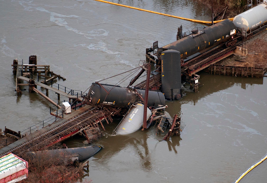 . Derailed freight train cars lay in water in Paulsboro, N.J., Friday, Nov. 30, 2012. People in three southern New Jersey towns were told Friday to stay inside after the freight train derailed and several tanker cars carrying hazardous materials toppled from a bridge and into a creek. (AP Photo/Cliff Owen)