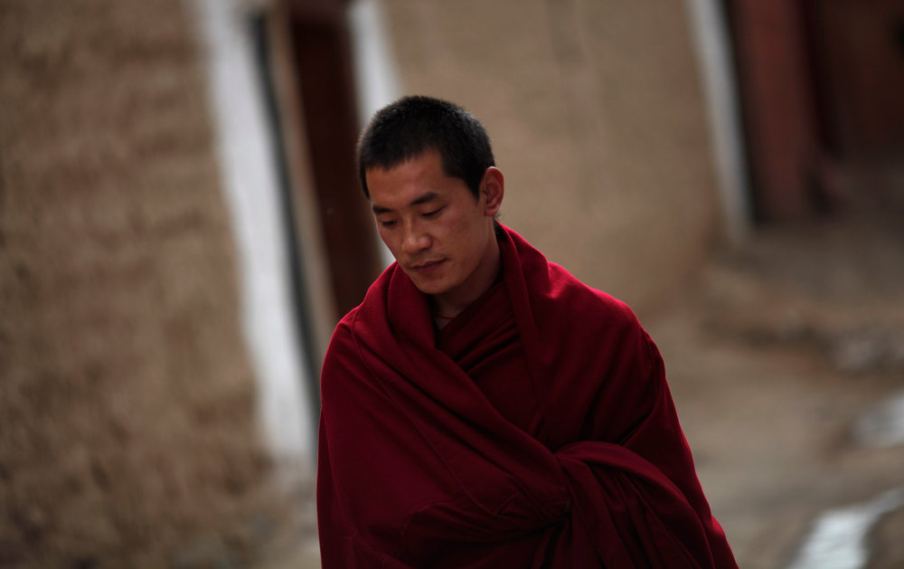 Description of . A Tibetan monk walks along an alley in Labrang Monastery during Tibetan new year, in Xiahe county, Gansu Province, February 11, 2013. Tibetans in a northwest part of China which has been a focus of self-immolation protests against Chinese rule marked a low-key lunar New Year on Monday, with many saying celebrations were inappropriate while the burnings continued. At least 20 people have set themselves on fire in the region around Xiahe in Gansu province over the last year, according to exiles and rights groups. Xiahe is home to a large ethnically Tibetan population and also to the monastery at Labrang, one of the most important centres for Tibetan Buddhism. The Tibetan lunar new year is supposed to be a time for celebration, but many Tibetans who spoke to Reuters in Xiahe said there would be no entertainment this year. REUTERS/Carlos Barria