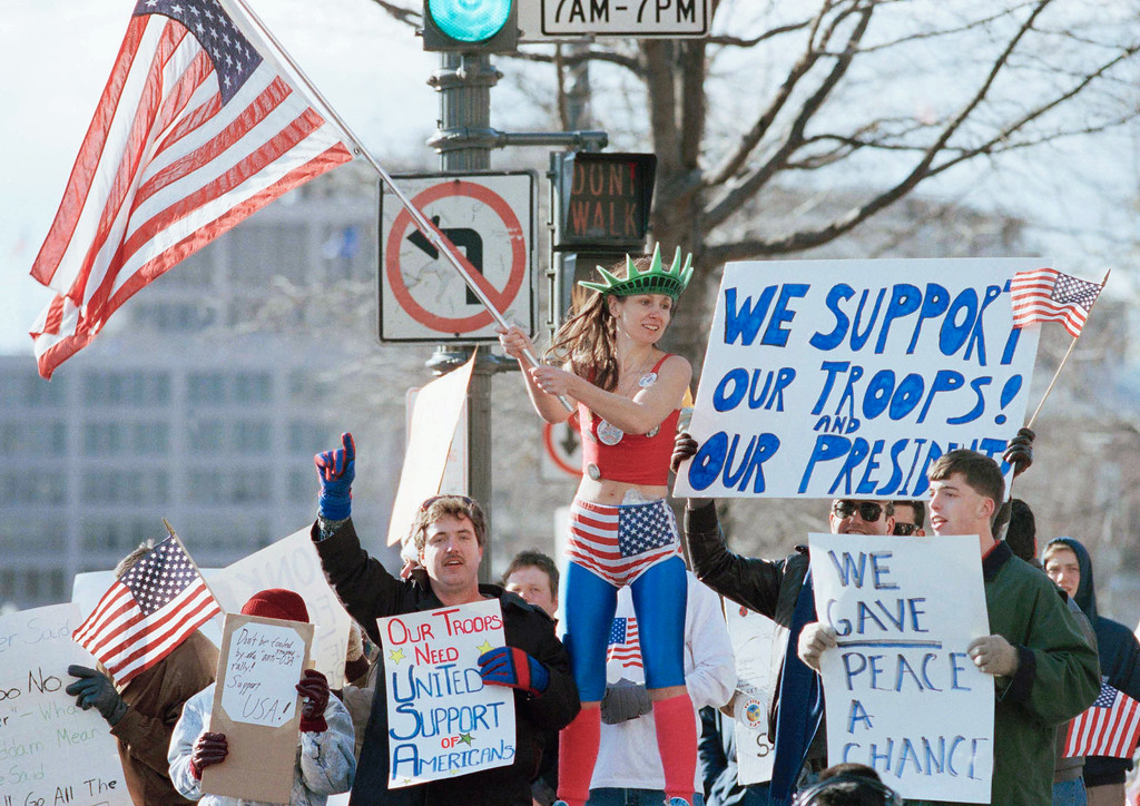 . A demonstrator dressed in an American flag outfit waves a flag along with other demonstrators in support of the troops in the Gulf across from the White House in Washington, Monday, Jan. 21, 1991. Several demonstrators shouted and sounded horns in support of the troops. (AP Photo/Steve Helber)