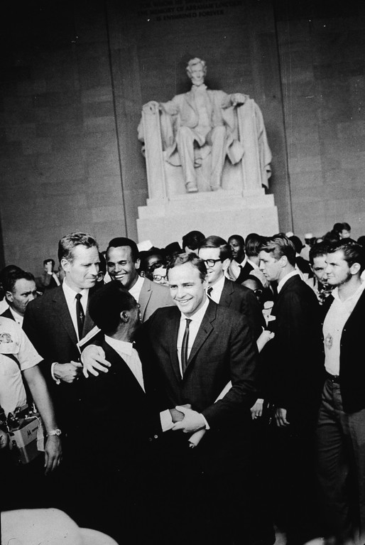 . American actor Marlon Brando (1924 - 2004) stands with his arm around poet James Baldwin, surrounded by actors Charlton Heston (L), Harry Belafonte and others gathered at the Lincoln Memorial during the Civil Rights March on Washington, D.C., August 28, 1963. (Photo by Hulton Archive/Getty Images)