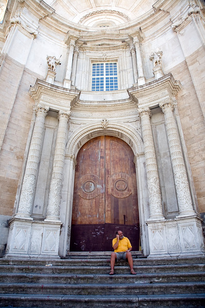 Everyday scene with the impressive baroque background of the facade of Cadiz Cathedral, Spain.