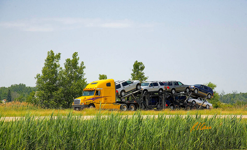 Trucks: Semi tractor hauls new cars south from Michigan factory on US23 south of Ann Arbor, June 2006.