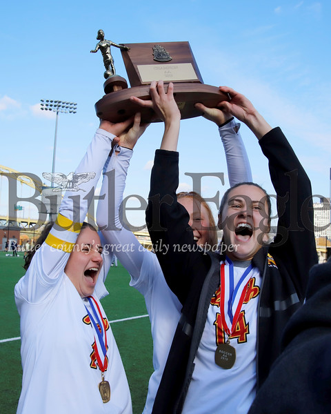North Catholic's Emma Kunzmann (right), Tori Michalski and Maddie Laird(left) raise the WPIAL Class 2A girls soccer trophy Saturday at Highmark Stadium in Pittsburgh. The Trojans topped Yough 1-0 in double overtime. Seb Foltz/Butler Eagle