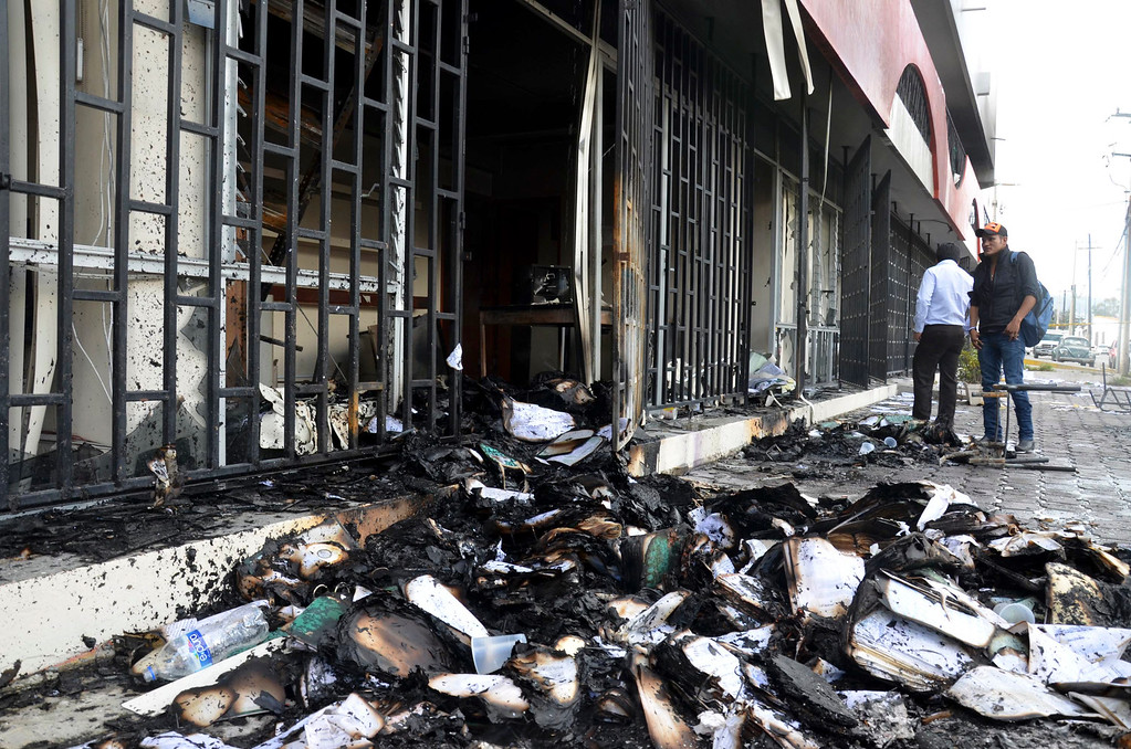. Burnt documents lie outside of the state comptroller\'s building after protesters torched the building in the state capital city of Chilpancingo, Mexico, Wednesday Nov. 12, 2014. (AP Photo/Alejandrino Gonzalez)