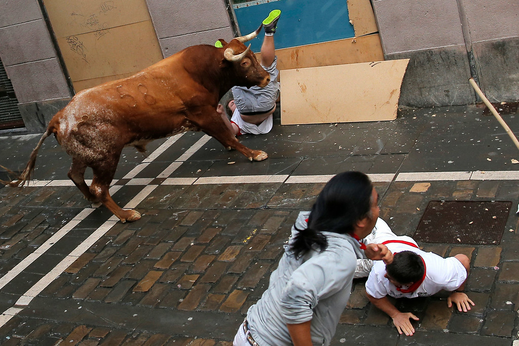 . A reveler is tossed by a Miura fighting bull as other fall during the running of the bulls at the San Fermin festival, in Pamplona, Spain, Monday, July 14, 2014. (AP Photo/Andres Kudacki)