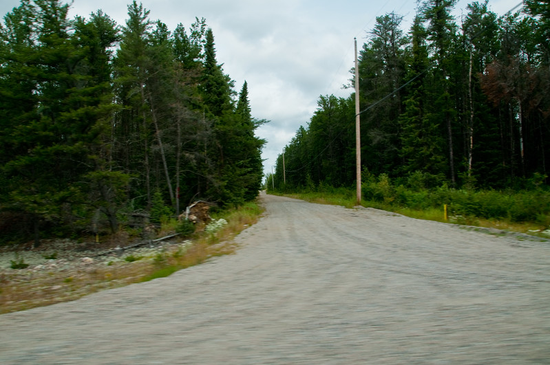 """While driving on the """"highway"""", we'd often see small side roads and/or driveways leading off into who-knows-what? This was actually one of the more """"civilized"""" loking ones... they even appear to have phone and power lines."""