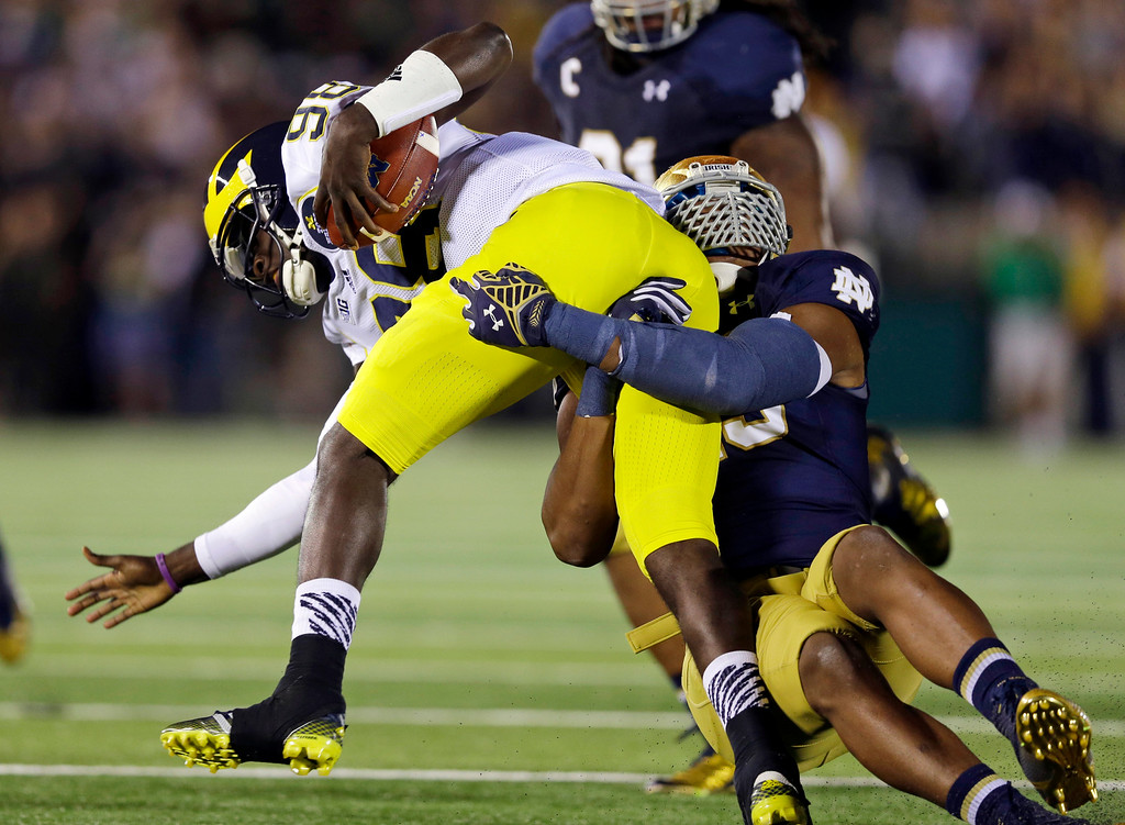 . Michigan quarterback Devin Gardner is sacked by Notre Dame defensive lineman Romeo Okwara, right, during the first half of an NCAA college football game in South Bend, Ind., Saturday, Sept. 6, 2014. (AP Photo/Michael Conroy)