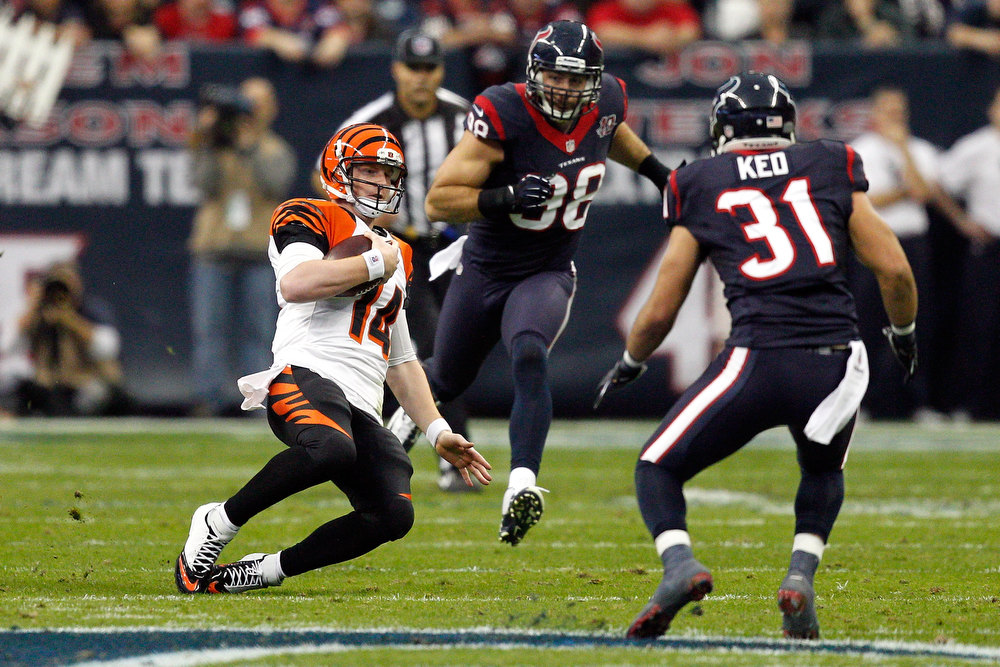 Description of . Andy Dalton #14 of the Cincinnati Bengals runs for 12-yards in the first half against Shiloh Keo #31 of the Houston Texans during their AFC Wild Card Playoff Game at Reliant Stadium on January 5, 2013 in Houston, Texas.  (Photo by Bob Levey/Getty Images)