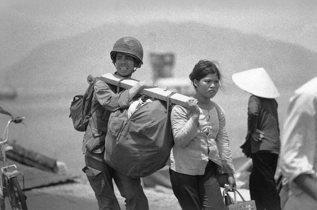 . A Saigon government soldier and his wife carry their possessionson on a pole as they disembark on March 30, 1975 from their ship that evacuated them form Danang before it fell to communist forces. (AP Photo)