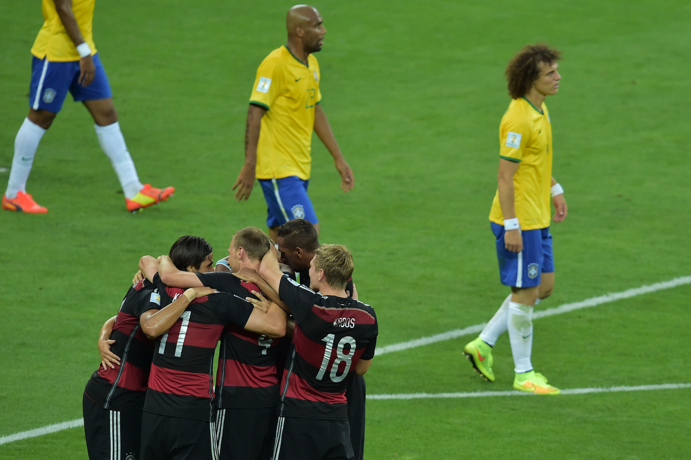 . Germany\'s players celebrate a goal by Germany\'s midfielder Sami Khedira (bottom L) during the semi-final football match between Brazil and Germany at The Mineirao Stadium in Belo Horizonte during the 2014 FIFA World Cup on July 8, 2014. (GABRIEL BOUYS/AFP/Getty Images)