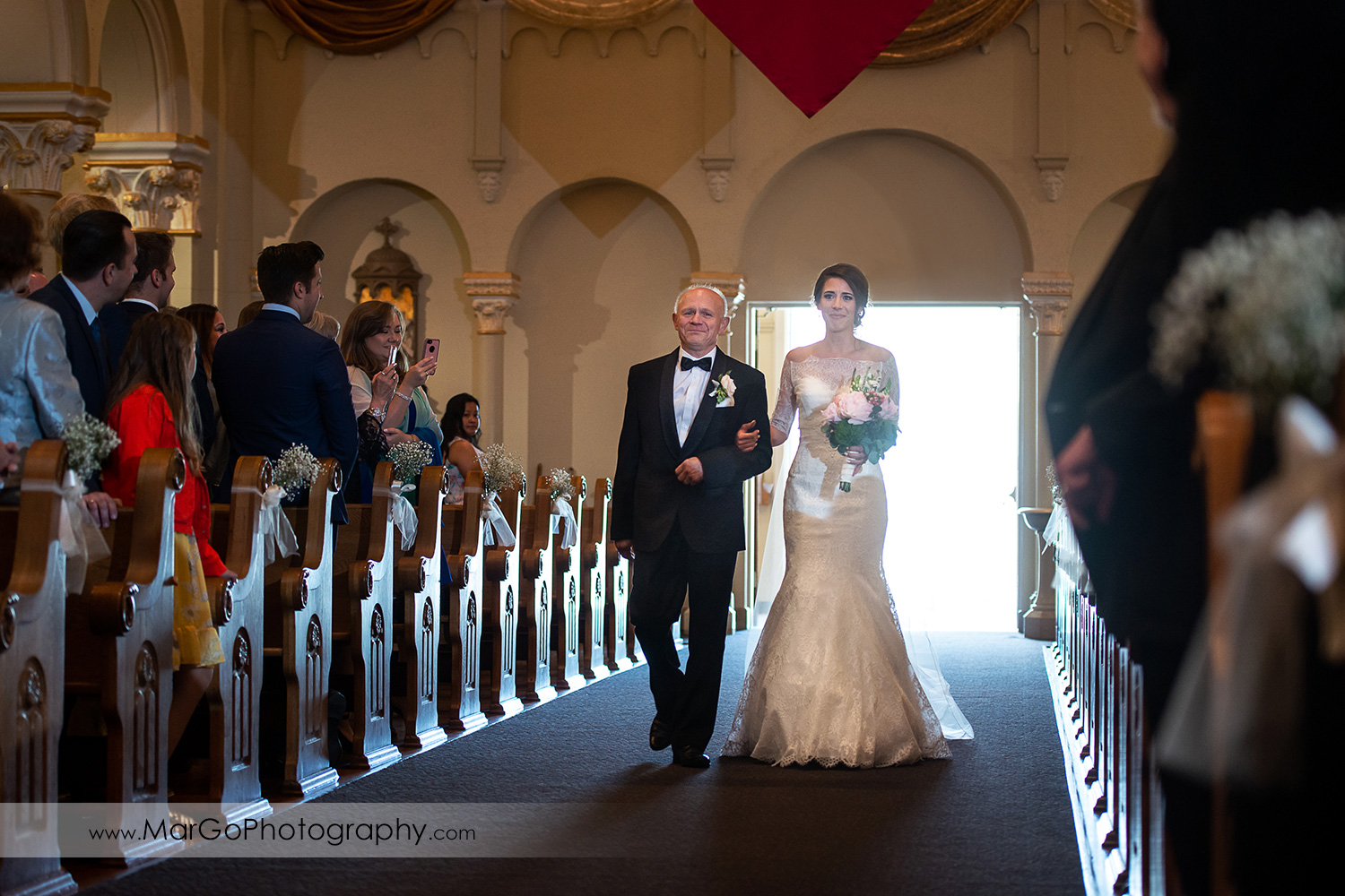 bride and her father walking down the aisle during wedding ceremony at Oakland Church of Saint Leo the Great
