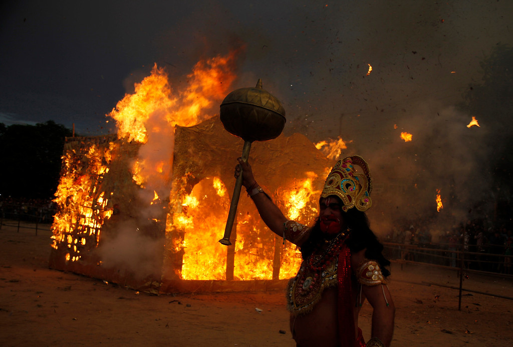 . An Indian artist dressed as Hindu monkey god Hanuman stands near a burning effigy of Lanka, the abode of demon king Ravana, during Dussehra festivities in Jammu, India, Sunday, Oct. 13, 2013. Dussehra festival commemorates the victory of Hindu god Rama over Ravana. The burning of effigies of Ravana, signifying the victory of good over evil, brings the festivities to a close.(AP Photo/Channi Anand)