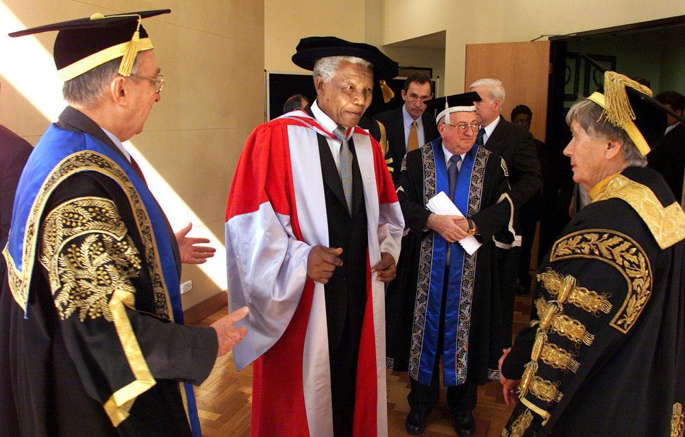 Description of . Nobel Peace Prize winner Nelson Mandela, center, chats with Prof. Dame Leonie Kramer, right, vice chancellor of the University of Sydney, and Sir Gerard Brennan, left, chancellor of the University of Technology, after the former South African leader received two honorary doctorates at Sydney University Iin Sydney Monday, Sept. 4, 2000. Mandela received a Doctor of Laws from both the universities and will continue on his week-long tour of Australia, visiting Canberra and Melbourne later this week.  (AP Photo/David Gray, Pool)