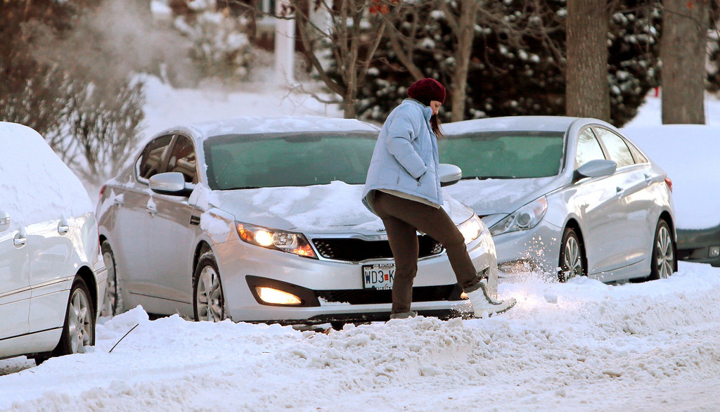 ". Sarah Smith tries to kick a clear path in the snow to free her trapped car on Tuesday, Jan. 7, 2014, outside of her apartment along the 5100 block of Waterman Blvd. in St. Louis. ""I had a shovel but it was stolen off my porch!, \"" said Smith.   (AP Photo/St. Louis Post-Dispatch, Laurie Skrivan)"