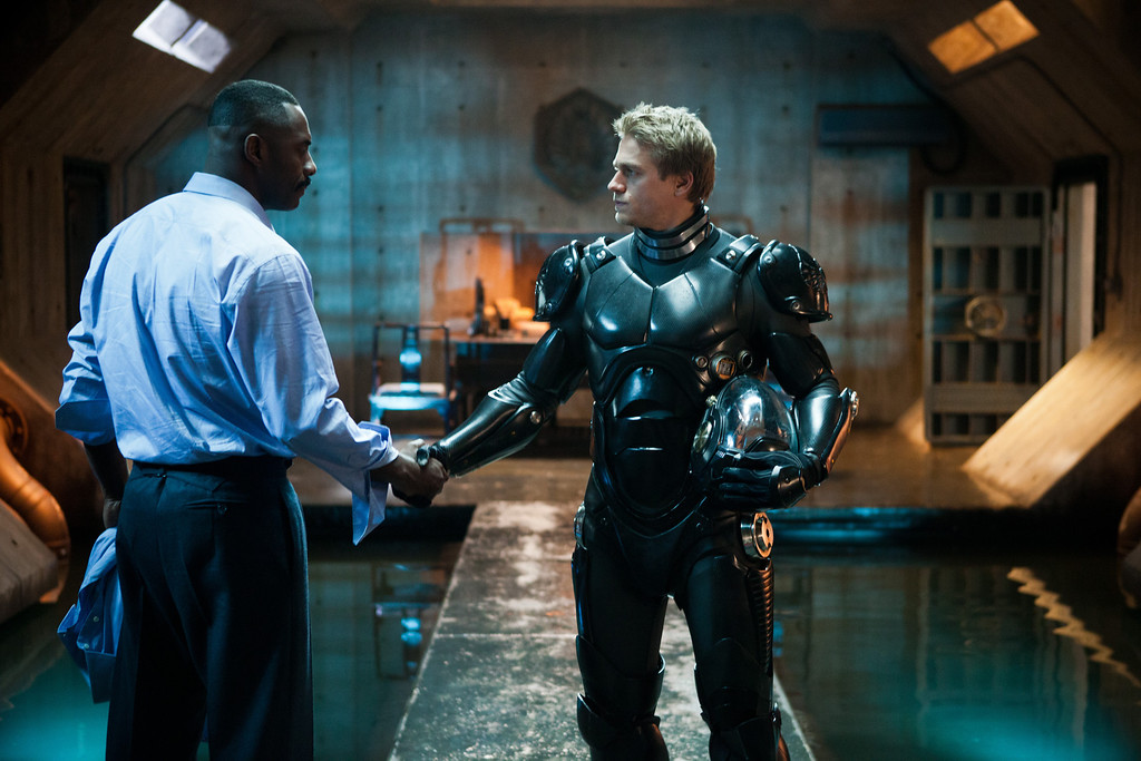 """. (L-r) IDRIS ELBA as Stacker Pentecost and CHARLIE HUNNAM as Raleigh Becket in Warner Bros. Pictures� and Legendary Pictures� sci-fi action adventure \""""PACIFIC RIM,\"""" a Warner Bros. Pictures release."""