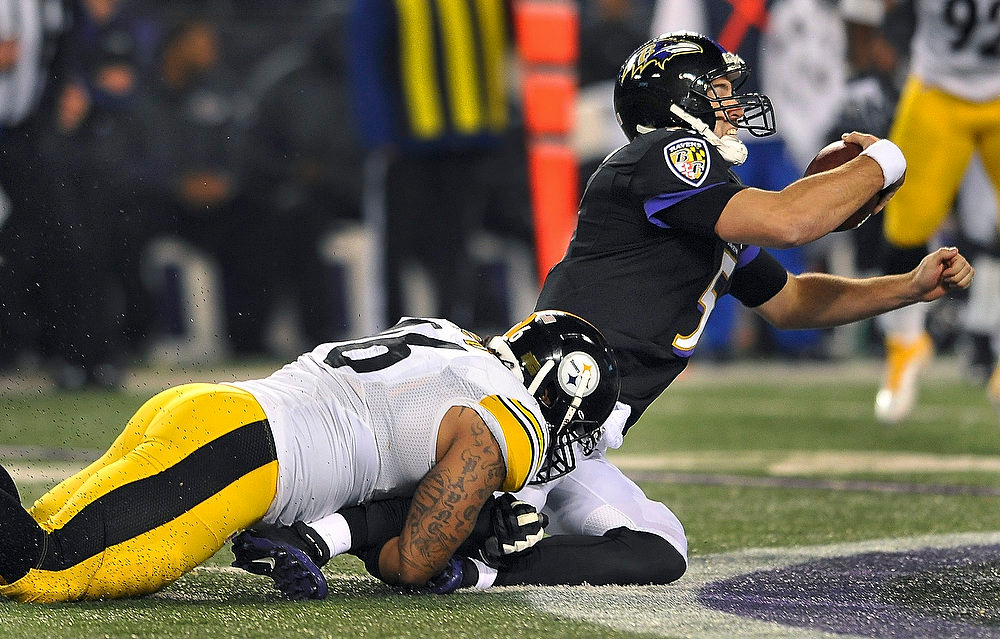 Description of . Pittsburgh Steelers defensive end Ziggy Hood, left, pulls down Baltimore Ravens quarterback Joe Flacco during the second half of an NFL football game in Baltimore, Sunday, Dec. 2, 2012. (AP Photo/Gail Burton)