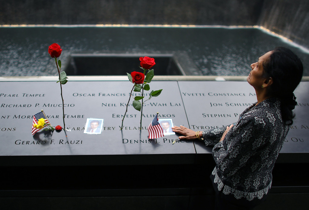 . A woman grieves at her husband\'s memorial at South Tower Memorial Pool during memorial observances on the 13th anniversary of the Sept. 11 terror attacks on the World Trade Center in New York, Thursday, Sept. 11, 2014.   Family and friends of those who died read the names of the nearly 3,000 people killed in New York, at the Pentagon and near Shanksville, Pennsylvania.  (AP Photo/The New York Times, Chang W. Lee, Pool)