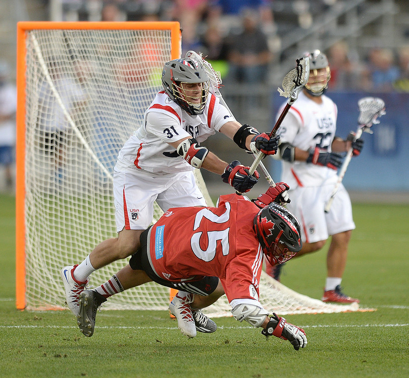 . United States midfielder David Lawson (31) knocked Canada midfielder Geoff Snider (25) to the ground in the first half. The United States took on Canada in the opening game of the FIL World Lacrosse Championships Thursday night, July 10, 2014.   Photo by Karl Gehring/The Denver Post