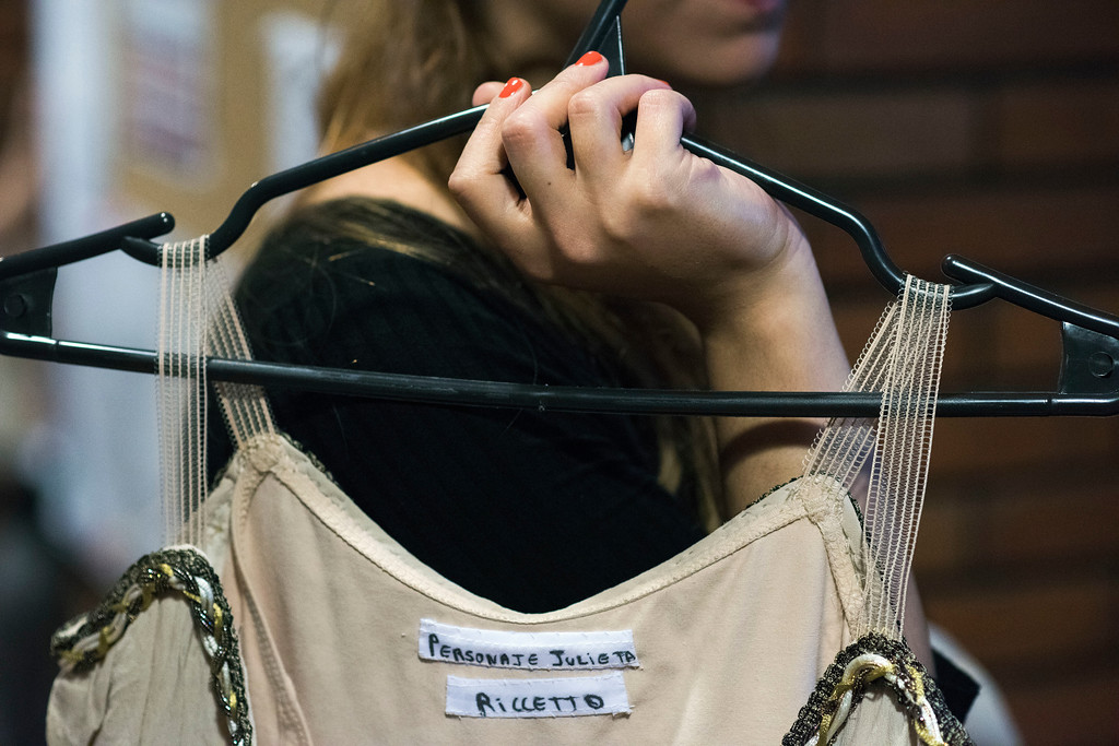 . In this Tuesday, Sept. 12, 2017 photo, a wardrobe worker carries a dress used by the Julieta character, used by principal dancer Maria Noel Riccetto, before rehearsal for Romeo and Juliet in Montevideo, Uruguay. About 70 professional dancers train under the eye of a man who wants to turn the ballet company of this small South American nation into one of the best in the world. (AP Photo/Matilde Campodonico)
