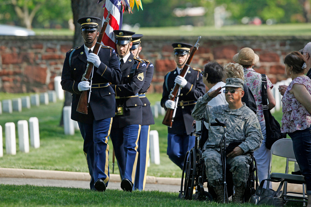 . U.S. Army Reservist 1st Lt. William Garcia, seated, right, salutes as the honor guard arrives at the gravesite of Army Pvt. William Christman, who was the first military burial at the cemetery, marking the beginning of commemorations of the 150th anniversary of Arlington National Cemetery in Arlington, Va., Tuesday, May 13, 2014.  (AP Photo)