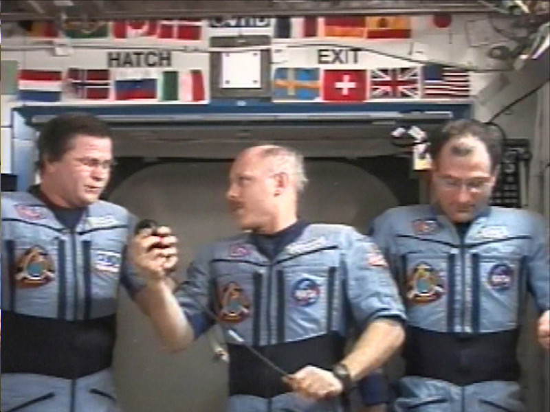 . In this image from television on Tuesday, Feb. 11, 2003 international space station commander Ken Bowersox, center, hands the microphone to Russian flight engineer Nikolai Budarin,left, during a news conference from the space station. At right is science officer Don Pettit. They said they\'ve shed tears for their friends who died aboard space shuttle Columbia,  but are now trying to move forward --though slowly.(AP Photo/NASA TV)