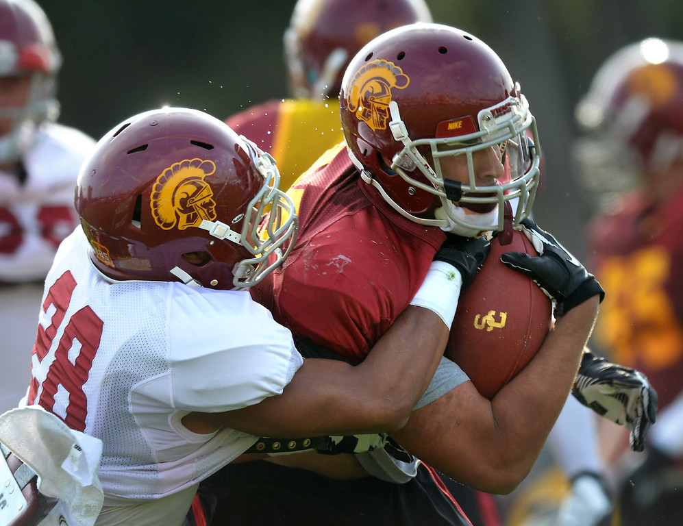 . USC DB Ryan Dillard tries to strip the ball from RB Ty Isaac during practice, Tuesday, March 25, 2014, at USC. (Photo by Michael Owen Baker/L.A. Daily News)