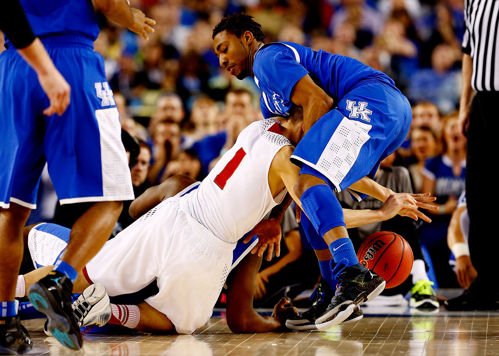 . ARLINGTON, TX - APRIL 05: James Young #1 of the Kentucky Wildcats and Ben Brust #1 of the Wisconsin Badgers battle for a loose ball during the NCAA Men\'s Final Four Semifinal at AT&T Stadium on April 5, 2014 in Arlington, Texas.  (Photo by Tom Pennington/Getty Images)