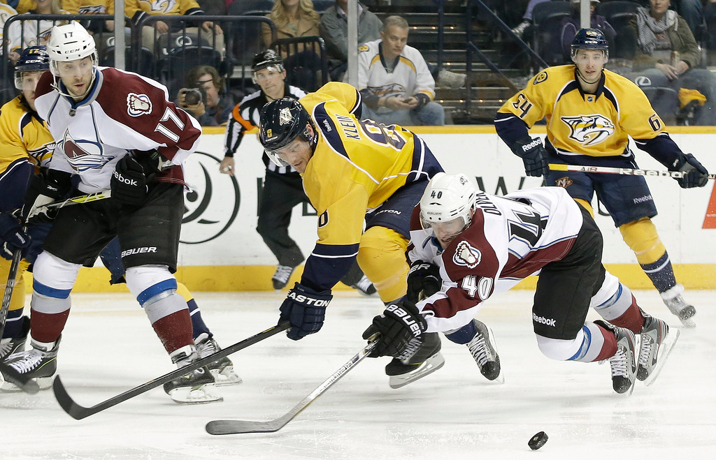 . Nashville Predators defenseman Kevin Klein (8) and Colorado Avalanche center Mark Olver (40) vie for the puck in the third period of an NHL hockey game Tuesday, April 2, 2013, in Nashville, Tenn. At left is Avalanche forward Aaron Palushaj (17), and at right is Predators defenseman Victor Bartley (64). (AP Photo/Mark Humphrey)