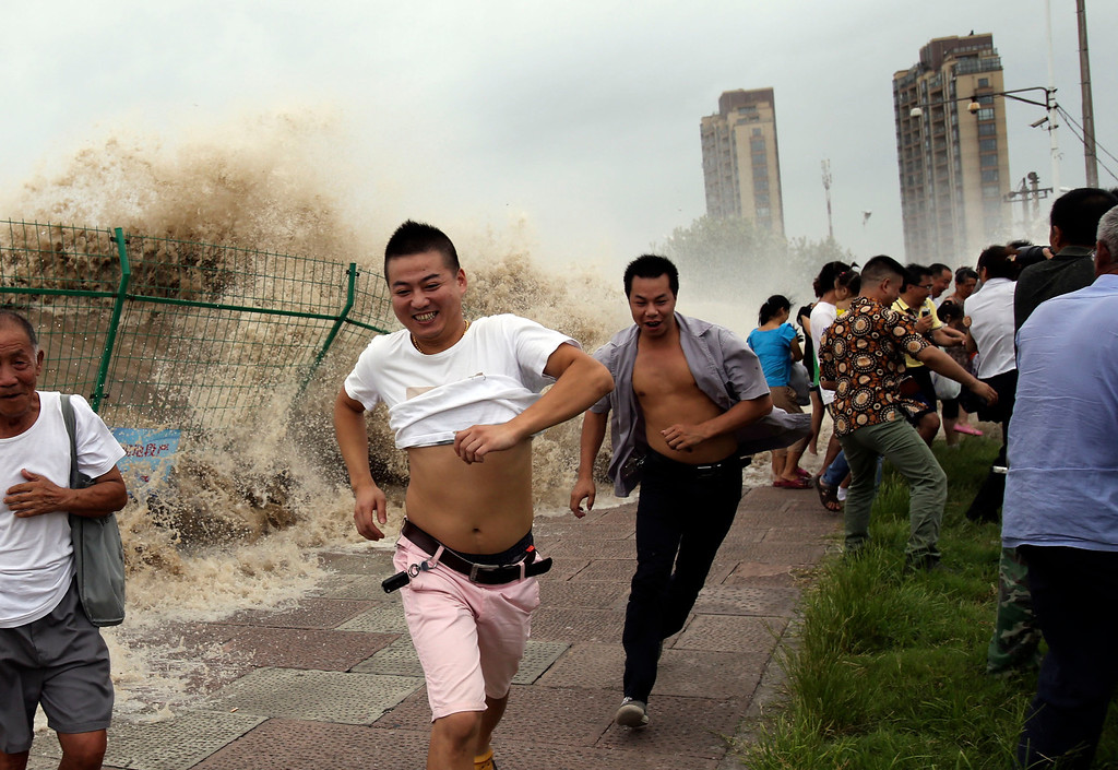 """. This picture taken on August 22, 2013 shows onlookers running away from huge waves from the \""""Haining tide\"""" - a daily occurrence when the river tides hit the banks of the city - as they surge higher than usual due to the influence of Typhoon Trami in the region in Haining, in eastern China\'s Zhejiang province. Typhoon Trami, the 12th typhoon to hit China this year, brought rainstorms and wreaked havoc in eastern China after landing in Fujian Province early on August 22.  The tides there have attracted spectators for the past two millennia, and it is the scene of an annual Tide-Watching Festival in late summer.      AFP PHOTOSTR/AFP/Getty Images"""