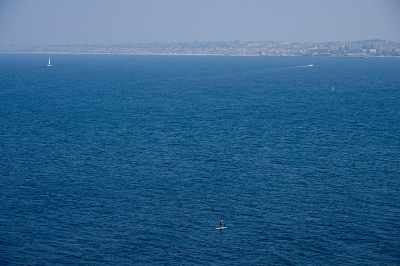 The same paddler, joined by three boats., in the Pacific Ocean, heading towards Redondo Beach.