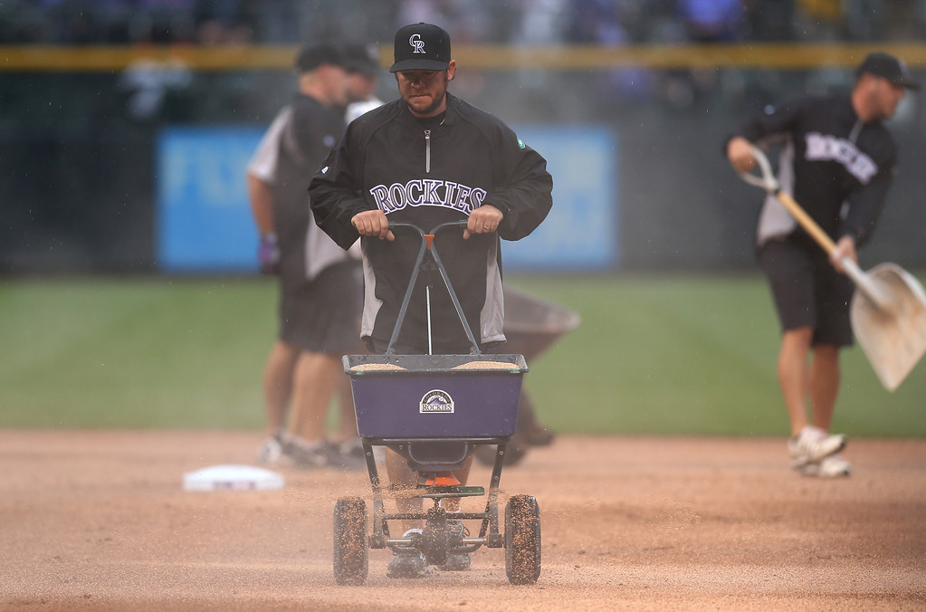 . As rains settles in over Coors Field, members of the maintenance crew use a water-absorbing substance on the infield as the Los Angeles Dodgers face the Colorado Rockies in the fourth inning of a baseball game in Denver on Sunday, June 8, 2014. (AP Photo/David Zalubowski)